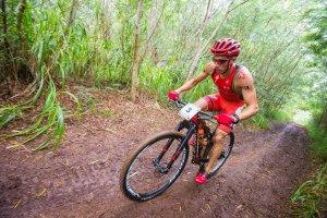 ciclista com roupa laranja em moutain bike em estrada de terra com mato ao fundo