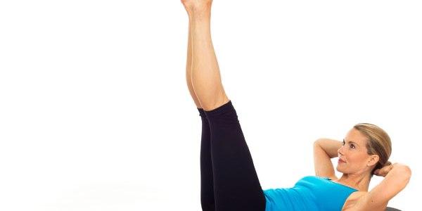 moça com blusa azul e calça preta, loira de coque. Deitada com pernas para o alto e braços atrás da cabeça