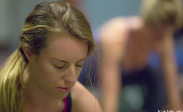 Moça loira com cabelo preso para baixo cobrindo o ombro direito. Blusapreta de alça. Close, olhos fechados e cabeça levemente abaixada para frente.