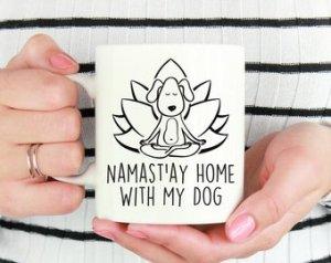 caneca branca com desenho de cachorro com pernas cruzadas a mãos sobre os joelhos em frente a uma flor de lotus com a inscrição: Namast'ay home with my dog
