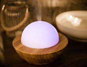 difusor de aroma com base de bambu e parte branca onde sai a fumaça