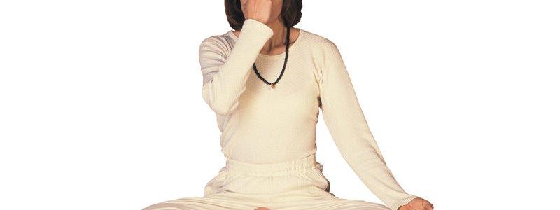 mulher de cabelos castanhos, olhos fechados, de branco em posição de lótus, tocando a testa com os dedos indicador e médio