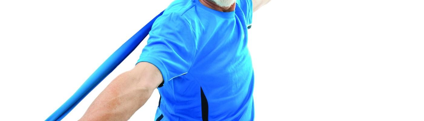 homem de blusa e calça azul, olhando para câmera e sorrindo, de barba e cabelos grisalhos, sentado em bola de Pilates azul, esticando uma tera band atrás das costas, fundo branco