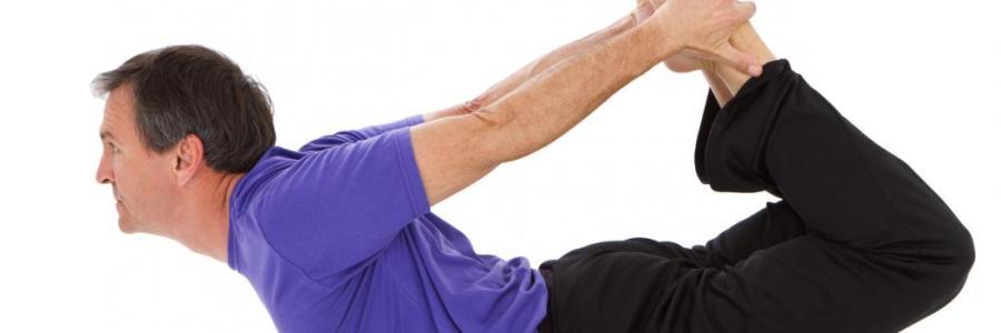 homem de blusa roxa e calça preta de perfil realizando postura onde segura os pés dobrando a coluna para trás e apoiando a pelvis no chão, fundo branco