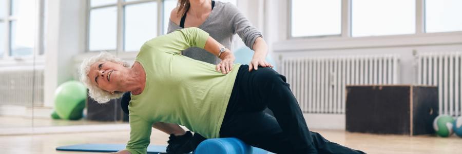 mulher idosa de calça preta e blusa verde deitada de lado em postura de Pilates em cima do rolinho com instrutora atrás auxiliando
